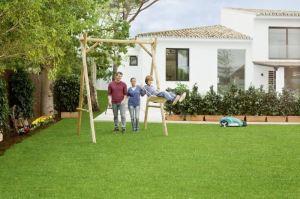 Familie im Garten, im Hintergrund ein Rasenmähroboter